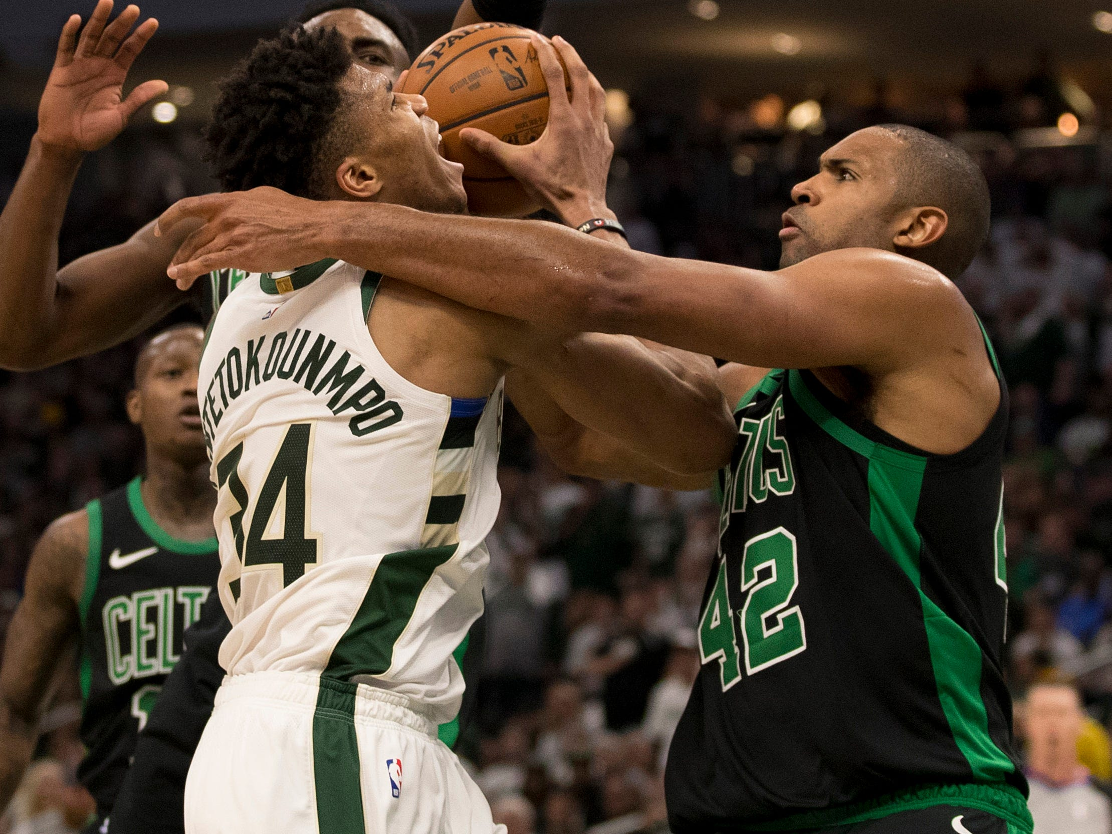 April 28: Celtics defender Al Horford (42) ties up Bucks forward Giannis Antetokounmpo (34) on a drive to the hoop during Game 1.