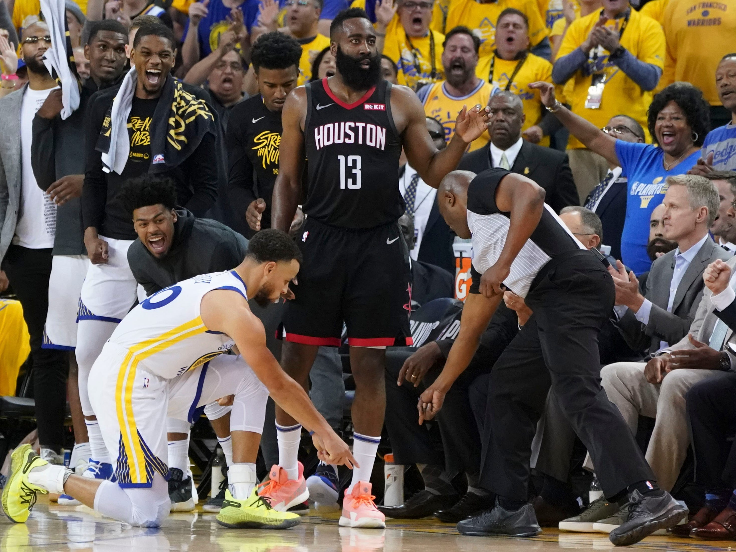 April 28: Warriors guard Steph Curry (30) helps out the ref and points to the spot where Rockets guard James Harden (13) stepped out of bounds and turned the ball over during Game 1