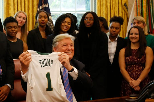 President Donald Trump holds a jersey given to him by the Baylor women's basketball team during a ceremony to celebrate its national championship.