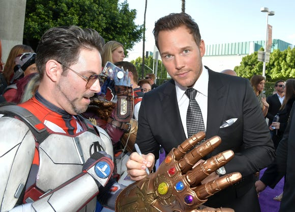 "Chris Pratt (right) signs a fan's Infinity Gauntlet at the L.A. premiere of ""Avengers: Endgame."""