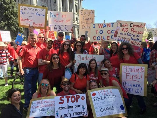 Dana Berge (seated in the first row, on the far right) rallies with her colleagues in Denver, Colorado, in April 2018.
