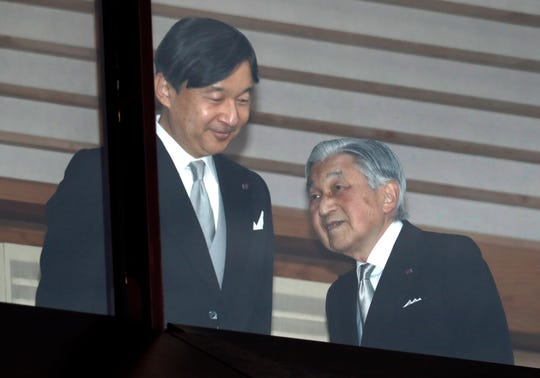FILE - In this Dec. 23, 2018, file photo, Japan's Emperor Akihito, right, accompanied by Crown Prince Naruhito, walks away after greeting well-wishers when they appeared on the balcony of the Imperial Palace to mark the emperor's 85th birthday in Tokyo. Akihito is ending his three-decade reign Tuesday, April 30, 2019 as he abdicates to his son, Crown Prince Naruhito, becoming the first to do so in 200 years, in a step nobody today has witnessed. (AP Photo/Eugene Hoshiko, File)