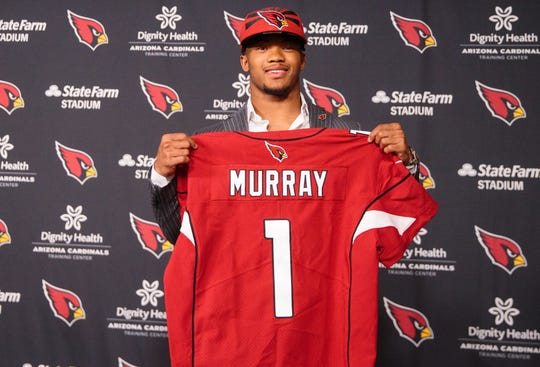 Kyler Murray poses for a photo holding his Cardinals jersey  after being drafted with the first overall pick.