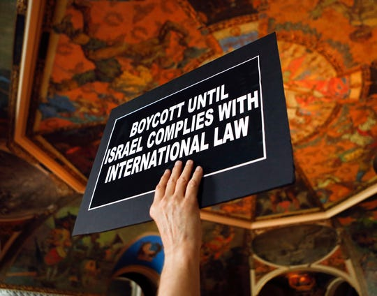 A man holds a sign during a rally in the War Room at the state Capitol on Wednesday, June 15, 2016, in Albany, N.Y. Critics of Israel's treatment of Palestinians protested Gov. Andrew Cuomo's executive order prohibiting state investments in any company that supports a boycott of Israel.
