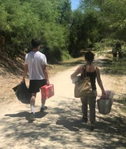 Thuan Le Elston and her son Kien-Tam help carry Easter party donations on April 17, 2019, from Texas to the border village of Boquillas, Mexico.