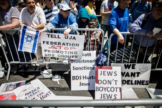 Protesters against the Boycott, Divestment and Sanctions movement stand behind a police barricade during the Celebrate Israel Parade in New York in 2014.