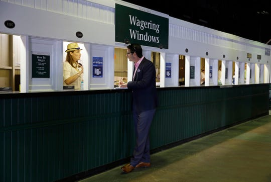 A man places a bet before the 141st running of the Kentucky Derby at Churchill Downs.