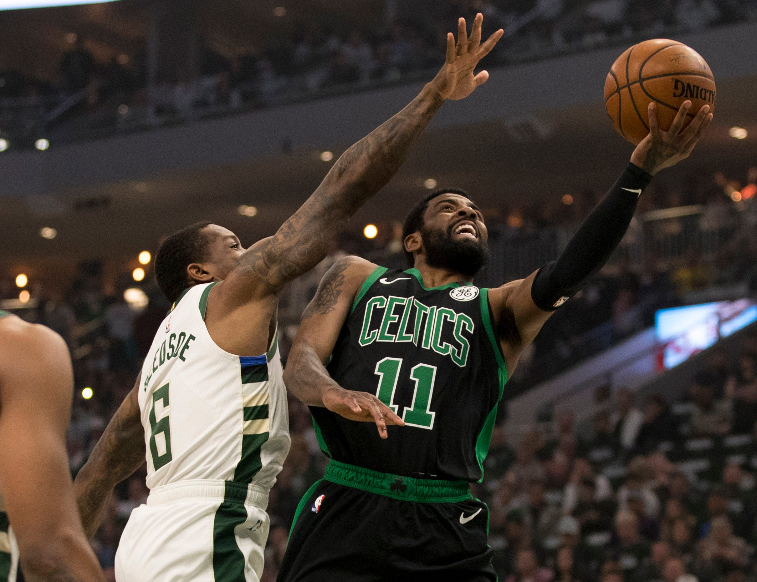 April 28: Celtics guard Kyrie Irving (11) drives to the hop against Bucks defender Eric Bledsoe (6) during Game 1 in Milwaukee.