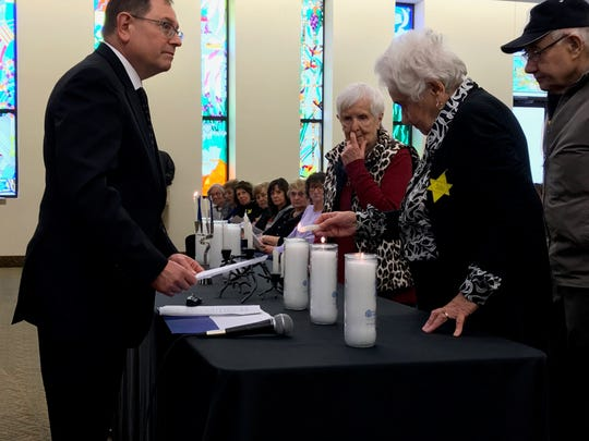 Holocaust survivors light candles during a service at the Congregation Ahavat Olam in Howell.