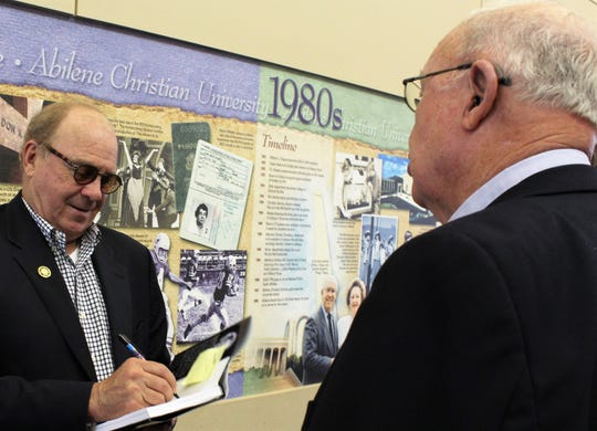 """Chris Christian, left, signs a copy of his new book """"A Grandmother's Prayer: Moments in a Music Life"""" for former Abilene Christian University dean Gene Linder."""