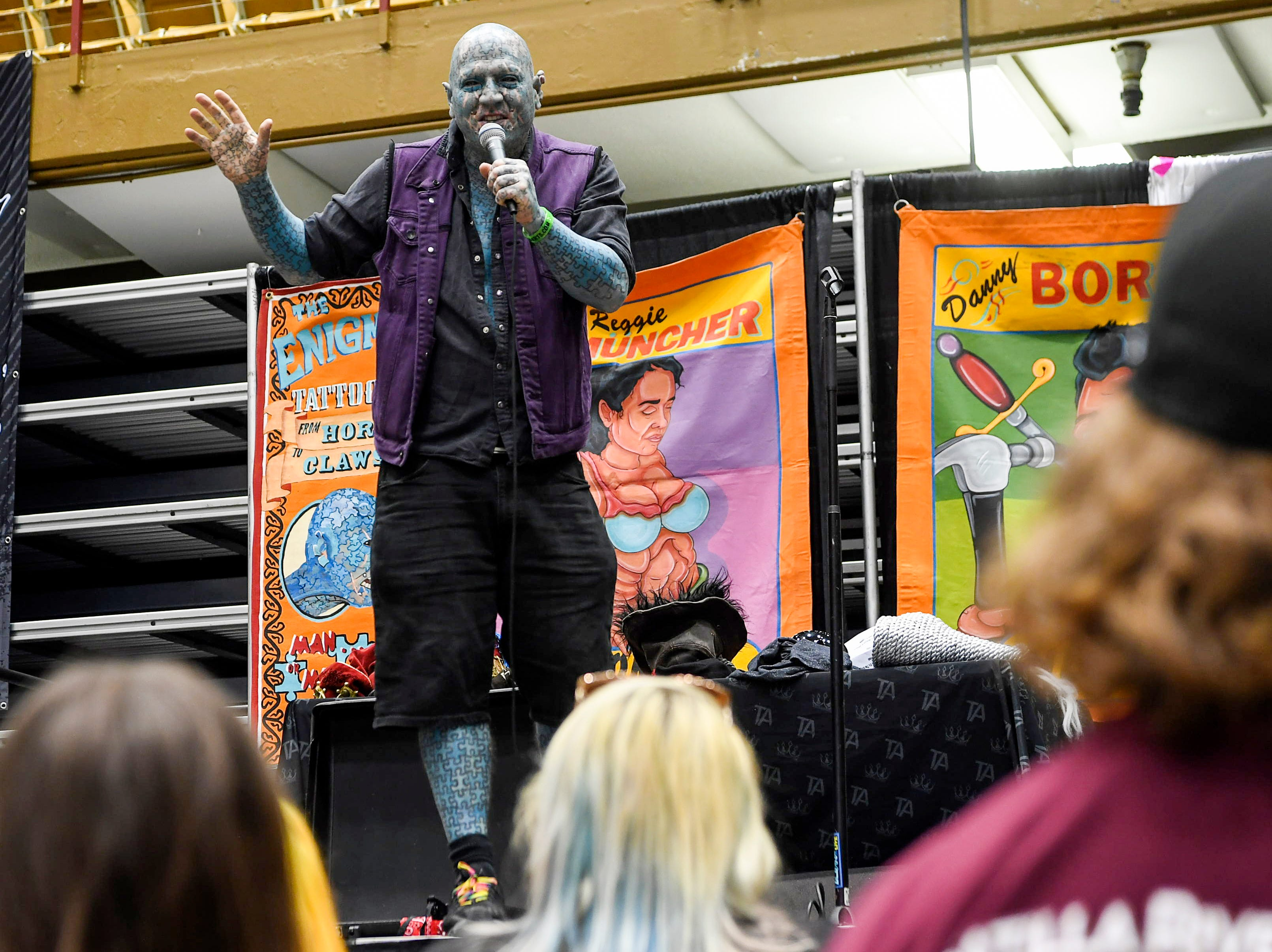 """Sideshow performer """"The Enigma,"""" who is covered in jigsaw puzzle tattoos, speaks to a crowd at the Asheville Tattoo Convention April 28, 2019."""