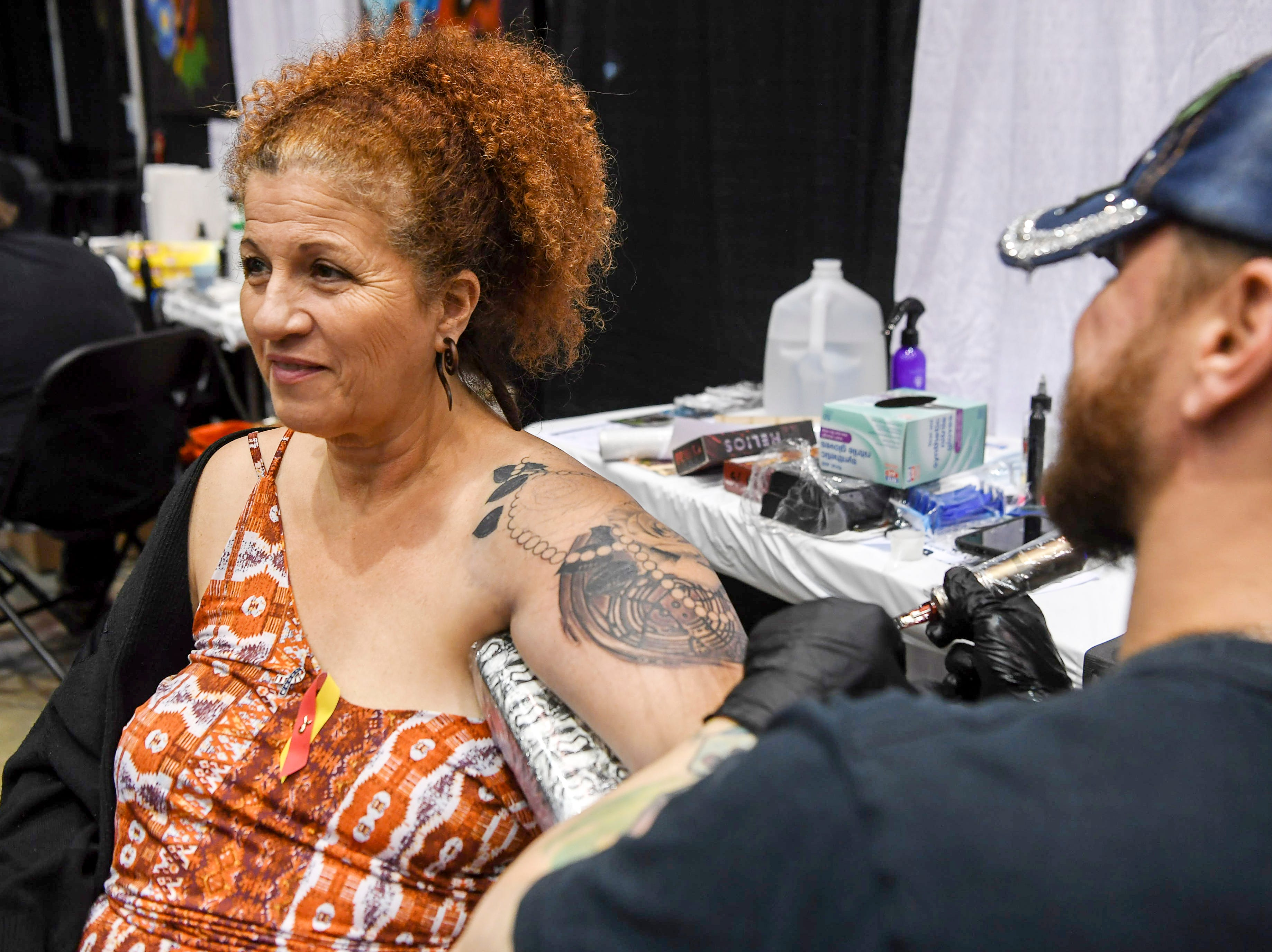 Vilma Williamson is tattoed by Dale Callahan of Hunter Gatherer Tattoo in Philadelphia during the Asheville Tattoo Convention April 28, 2019. Williamson traveled from Georgia to attend the convention.