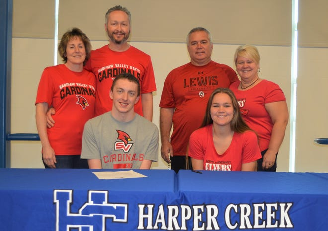 Harper Creek's Alex Piper, left, and Meredith Coon each signed a National Letter of Intent to compete in their respective sports in college, being joined by their parents. Piper will swim at Saginaw  Valley State University and Coon will play women's soccer at Lewis University.