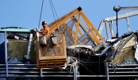With a portion of the broken crane on the roof behind, a worker suspended in a basket clears debris from a building damaged when the crane atop it collapsed a day earlier, Sunday, April 28, 2019, in Seattle. The construction crane fell from a building on Google's new campus during a storm that brought wind gusts, crashing down onto one of the city's busiest streets and killing multiple people. (AP Photo/Elaine Thompson)