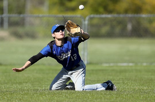 North Mason outfielder Preston Macomber falls to his knees and still makes a catch for an out against Klahowya on Monday, April 29, 2019.