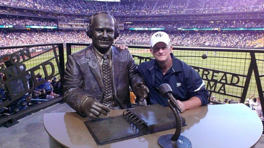 Paul Stensen sits by the statue of another iconic announcer, at the Dave Neihaus memorial at T-Mobile Park in Seattle.