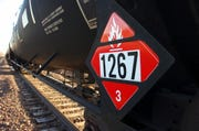 FILE - This Nov. 6, 2013, file photo, shows a warning placard on a tank car carrying crude oil near a loading terminal in Trenton, N.D. North Dakota officials are pressuring the state of Washington to back off from legislation requiring oil shipped by rail to have more of its volatile gases removed. Proponents of the bill awaiting Gov. Jay Inslee's signature say it will boost safety, but North Dakota officials worry it could hamper the nation's No. 2 oil producer. North Dakota's three members of Congress have asked Inslee to veto the bill. North Dakota regulators are considering a lawsuit.