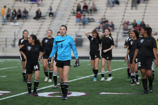 Team captain C.J. Graham (1) leads the Warlassies to the sidelines before the second half of a 3-0 win over Madison on senior night.