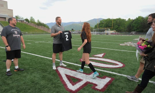 Owen senior Carly Campbell receives a jersey with her last name on the back from Warlassies head coach David Fiest on senior night.