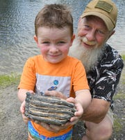 Colt Couch, who turns 3 next week, holds the mammoth tooth he discovered in Palm Bay alongside his grandfather, Monte Brigance.