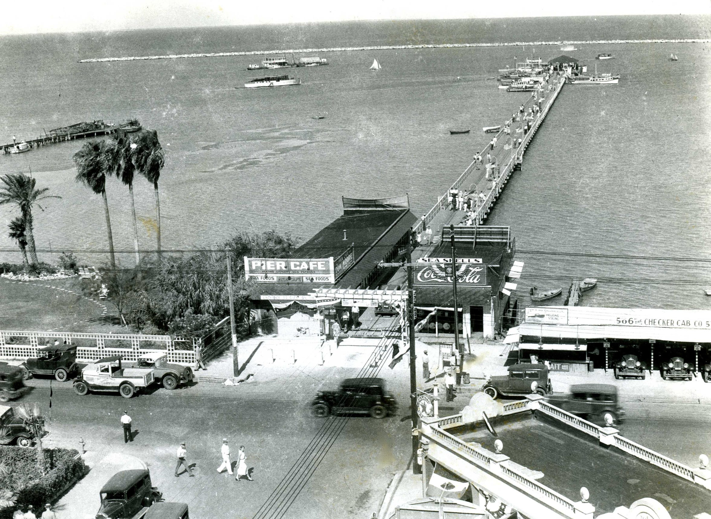 The original Pier Cafe in July 1932. The building, a remodeled fisherman's shack, sat at the foot of the city pleasure pier. Owner John Govatos built a new stucco building in 1932 to accomodate his growing clientele. The restaurant closed after the city began construction on the seawall in 1939.