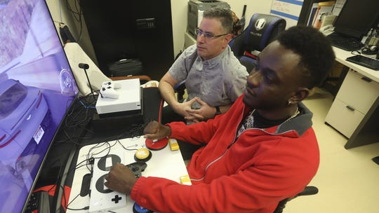 Mike Monthervil, U.S. Army veteran (front), and Jamie Kaplan, recreation therapist at James A. Haley Veterans' Hospital in Tampa, Fla. play a video game using a Xbox Adaptive Controller, set up with buttons and switches.