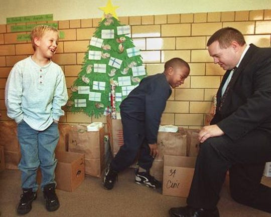 first graders at Central Elementary School in Fairfield in 1997 share a laugh with Charles Wiedenmann, Superintendant of Fairfield Schools as they load boxes of donated food for the school's Holiday Basket.