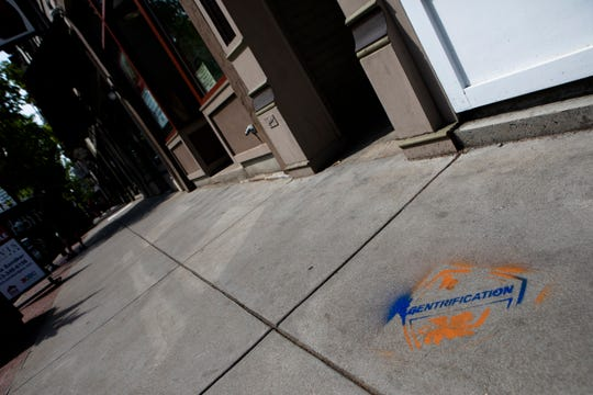 "A view of Graffiti reading ""Gentrification"" in FC Cincinnati colors is left on a sidewalk in the 1400 block of Vine Street in Over The Rhine on Tuesday, April 30, 2019."