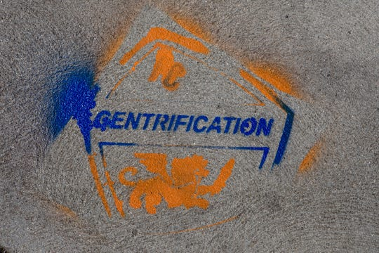 """A view of Graffiti reading """"Gentrification"""" in FC Cincinnati colors is left on a sidewalk in the 1400 block of Vine Street in Over The Rhine on Tuesday, April 30, 2019."""