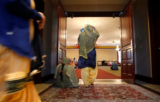 Women walk into the main hall at the Guru Nanak Society of Greater Cincinnati in West Chester for a prayer service to honor a  Sikh family who were found dead at their apartment.