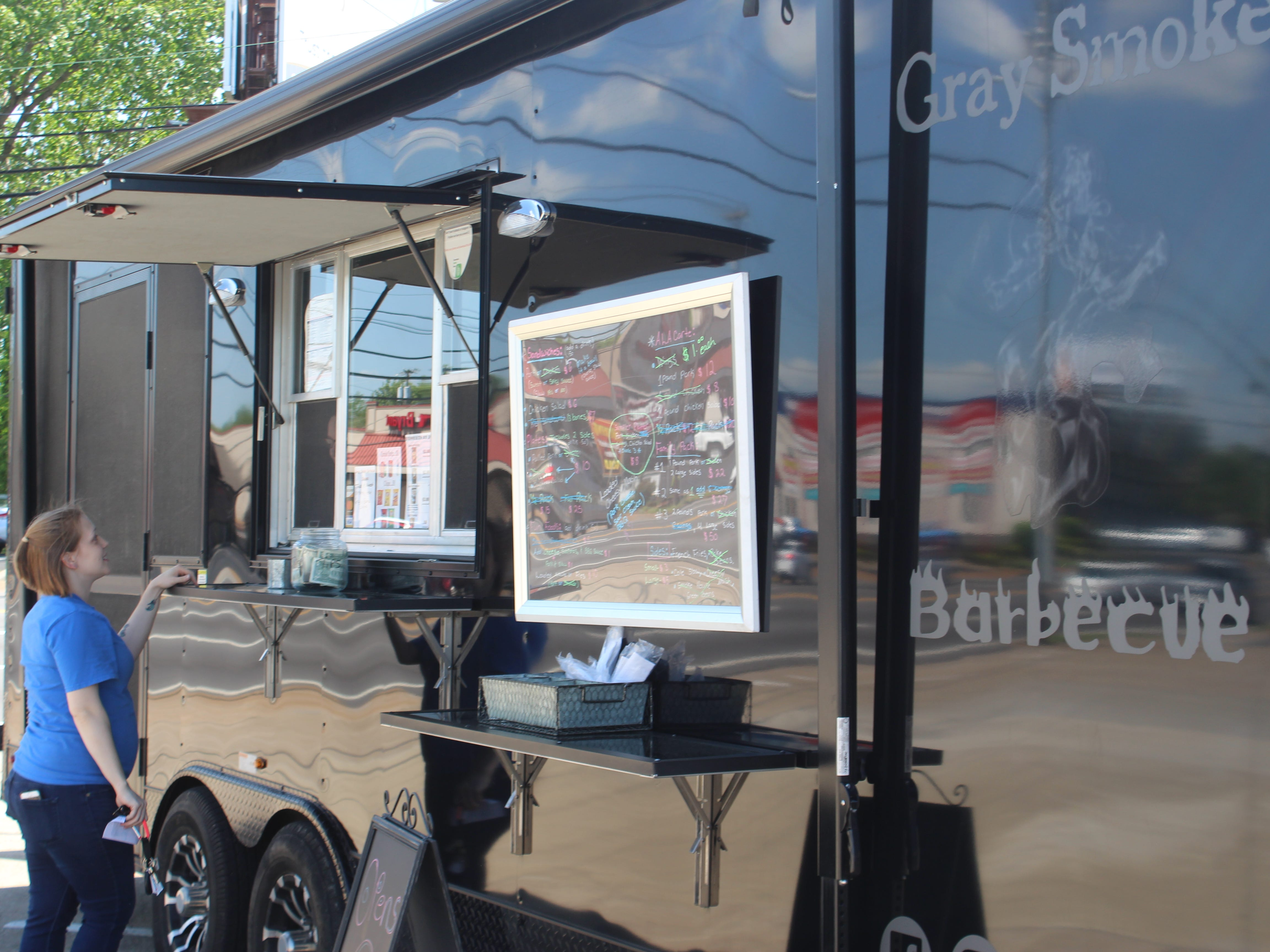 A customer waits for her order at the Gray Smoke Barbecue food truck on April 26, 2019.