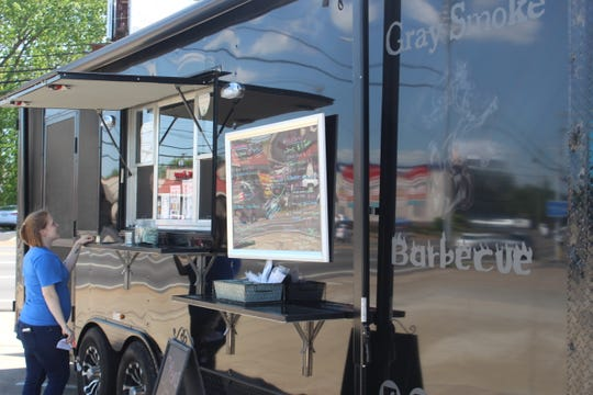 A customer waits for her order at the Gray Smoke Barbecue food truck on April 26.