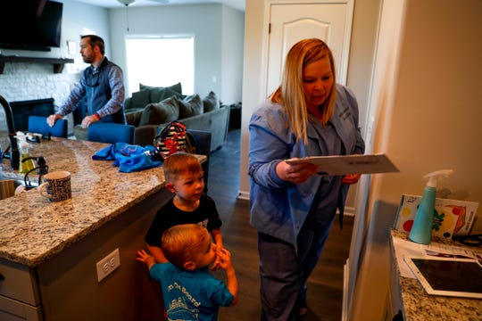 Brooke Gray holds up a letter that came in for her sons Benjamin and Sullivan Gray before she has to leave for work at Vanderbilt Hospital at the Gray household in Clarksville, Tenn., on Monday, April 29, 2019.