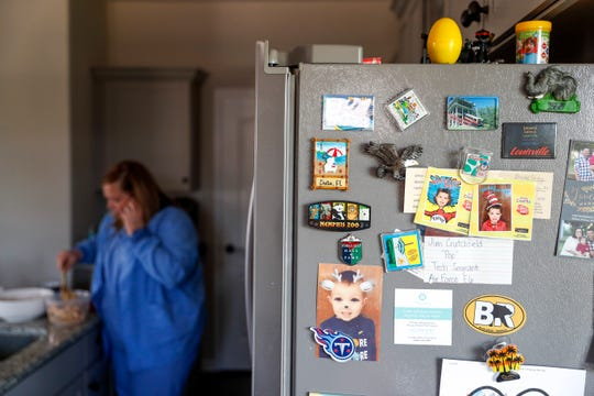Magnets, photos, and notes litter the side of the fridge while Brooke Gray, left, prepares a meal before leaving for her shift at Vanderbilt Hospital at the Gray household in Clarksville, Tenn., on Monday, April 29, 2019.