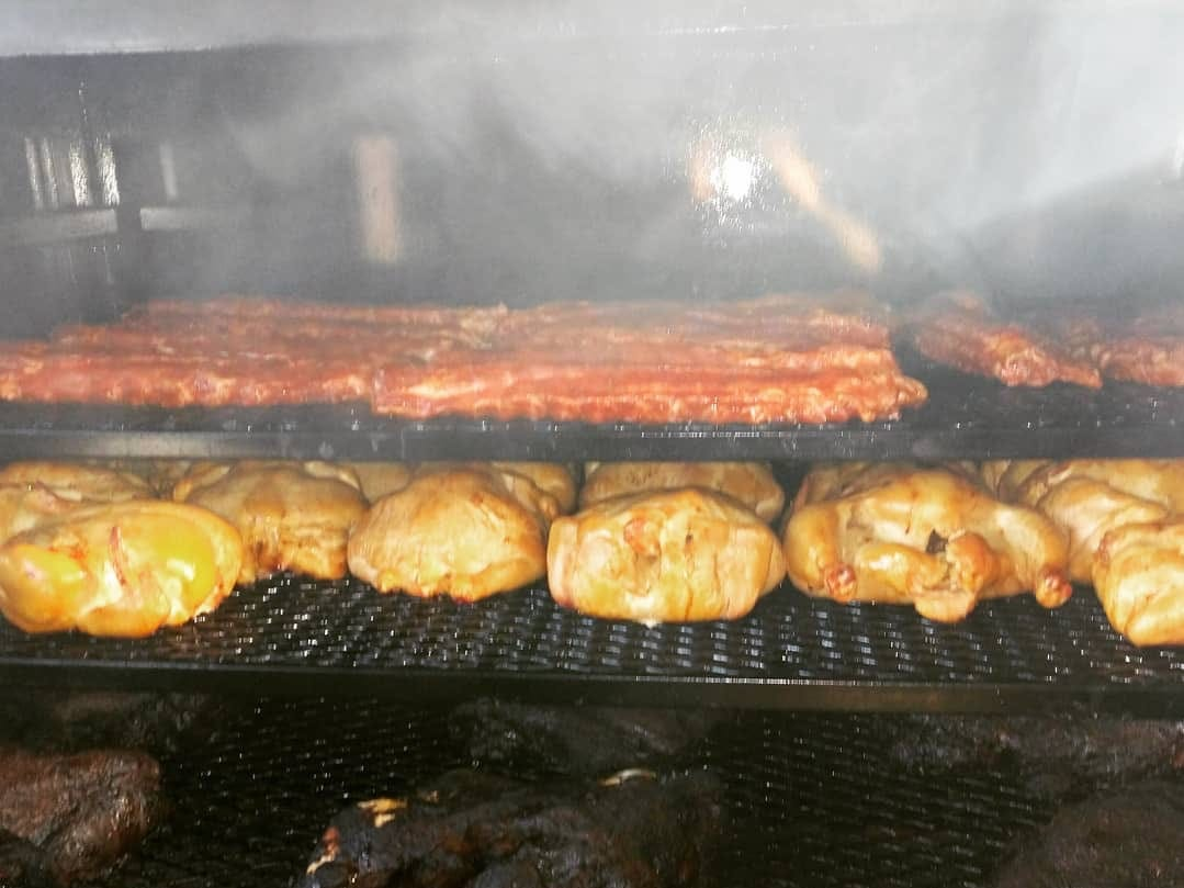 A variety of meats being smoked on the Gray Smoke Barbecue food trailer.