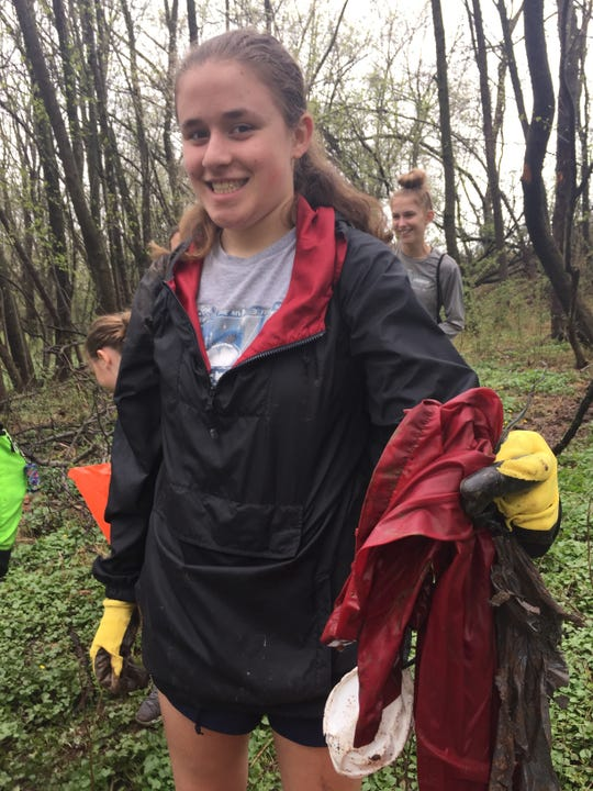 Gill St. Bernard's students at Raritan Headwaters Stream Cleanup Day on April 13. Here, Clare Janas of Califon, a member of the school's Environmental Club, holding a raincoat collected from the stream.