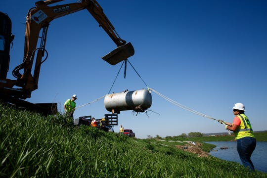 Kamailelani Napoleon with Environmental Restoration works with Bruce Amsden to remove an orphaned LP tank from the side of levee on Wednesday, April 24, 2019, outside of Pacific Junction. The EPA has been trying to find, organize, return or dispose of containers holding hazardous materials that were carried away by the flood waters.