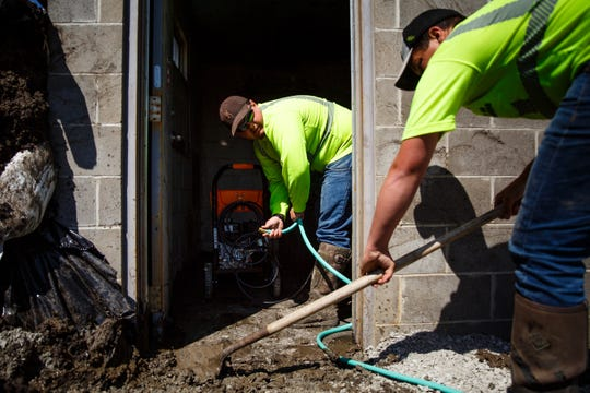 Wyatt Burge, 21 of Hamburg, left, and Trey Varellas, 24 of Hamburg work to clean out a pump station that had been swamped with flood water on Wednesday, April 24, 2019, in Hamburg.