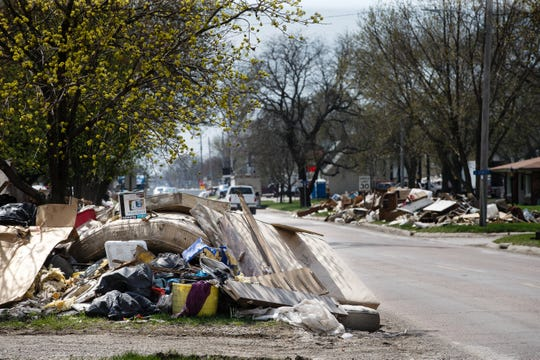 Residents belongings mix with flood damaged housing materials in piles along the side of the roads ready to be picked up and disposed of on Tuesday, April 16, 2019, in Hamburg.