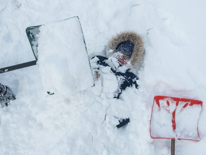 Ayanna Fulton of Flint reacts to the cold as her brother Dramell Fulton Jr. adds snow while burying her outside of their house on Billings St. in Flint on Tuesday, January 29, 2019 while home on their second snow day.