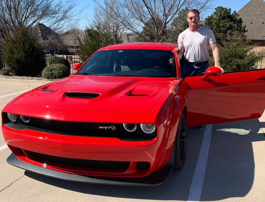 "Hugh Mullaney stands with his 2018 Challenger Hellcat Widebody near his home in Edmond, Oklahoma on January 15. The former Navy SEAL said the powerful car feels like it's ""going into battle."""