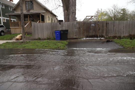 Water is seen flowing onto the street from Fox Creek along Ashland Street in Detroit on Tuesday, April 30, 2019.