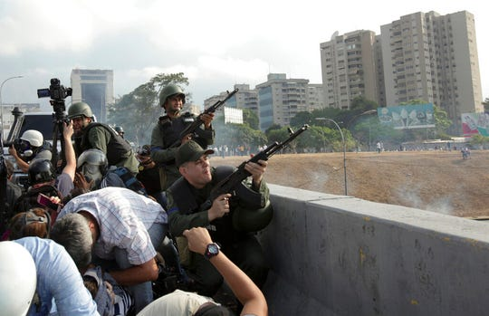 Rebel troops fire their weapons from an overpass outside La Carlota military airbase, Tuesday, April 30, 2019. Venezuelan opposition leader Juan Guaidó and jailed opposition leader Leopoldo Lopez took to the streets with a small contingent of heavily armed troops early Tuesday in a bold and risky call for the military to rise up and oust Maduro.