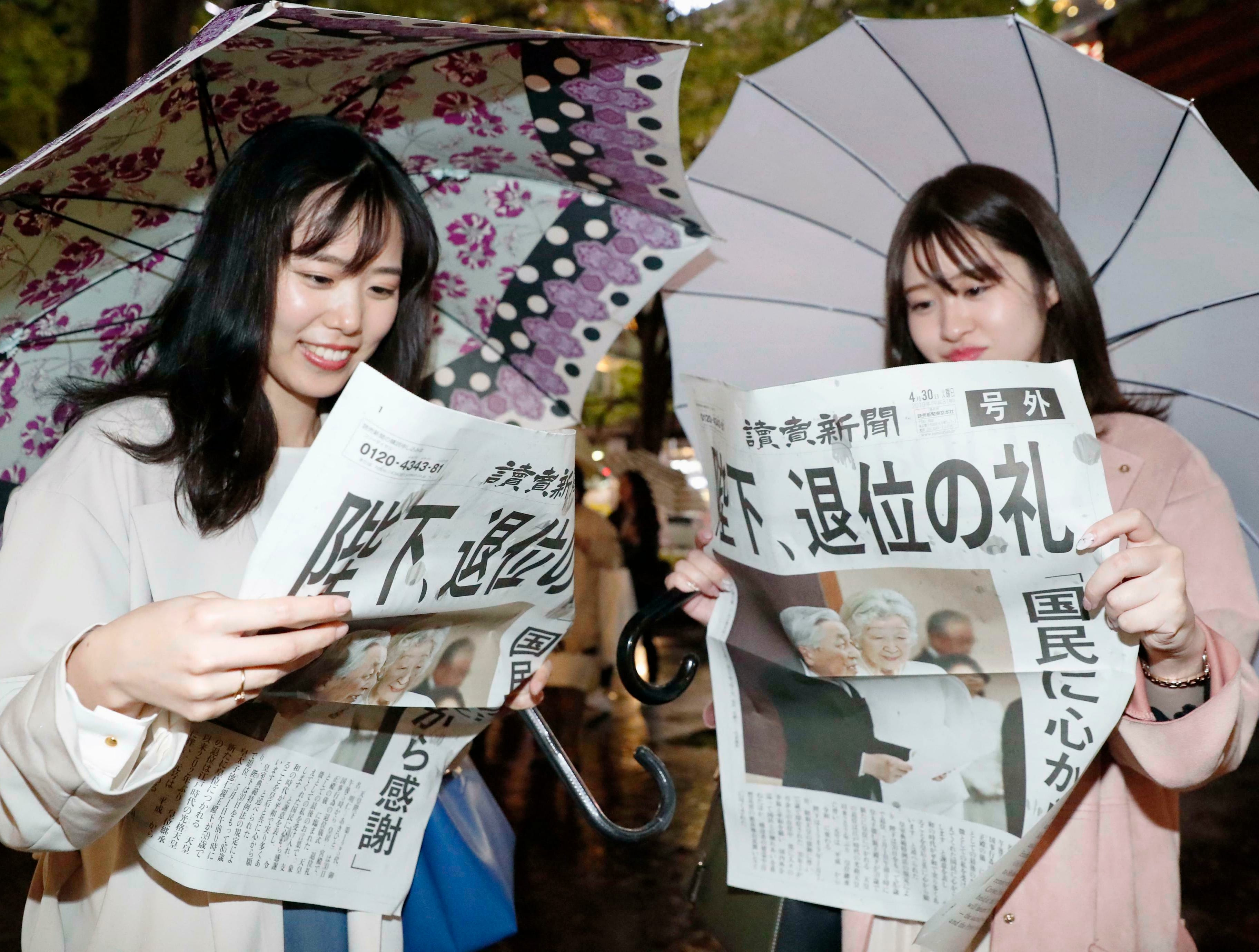 """Women read a copy of the extra edition of Yomiuri Shimbun newspaper reporting Emperor Akihito's abdication in Tokyo Tuesday, April 30, 2019.  The emperor made the announcement at a palace ceremony Tuesday in his final address, as the nation embraced the end of his reign with reminiscence and hope for a new era. The headline reads """"Emperor, abdication ritual."""""""