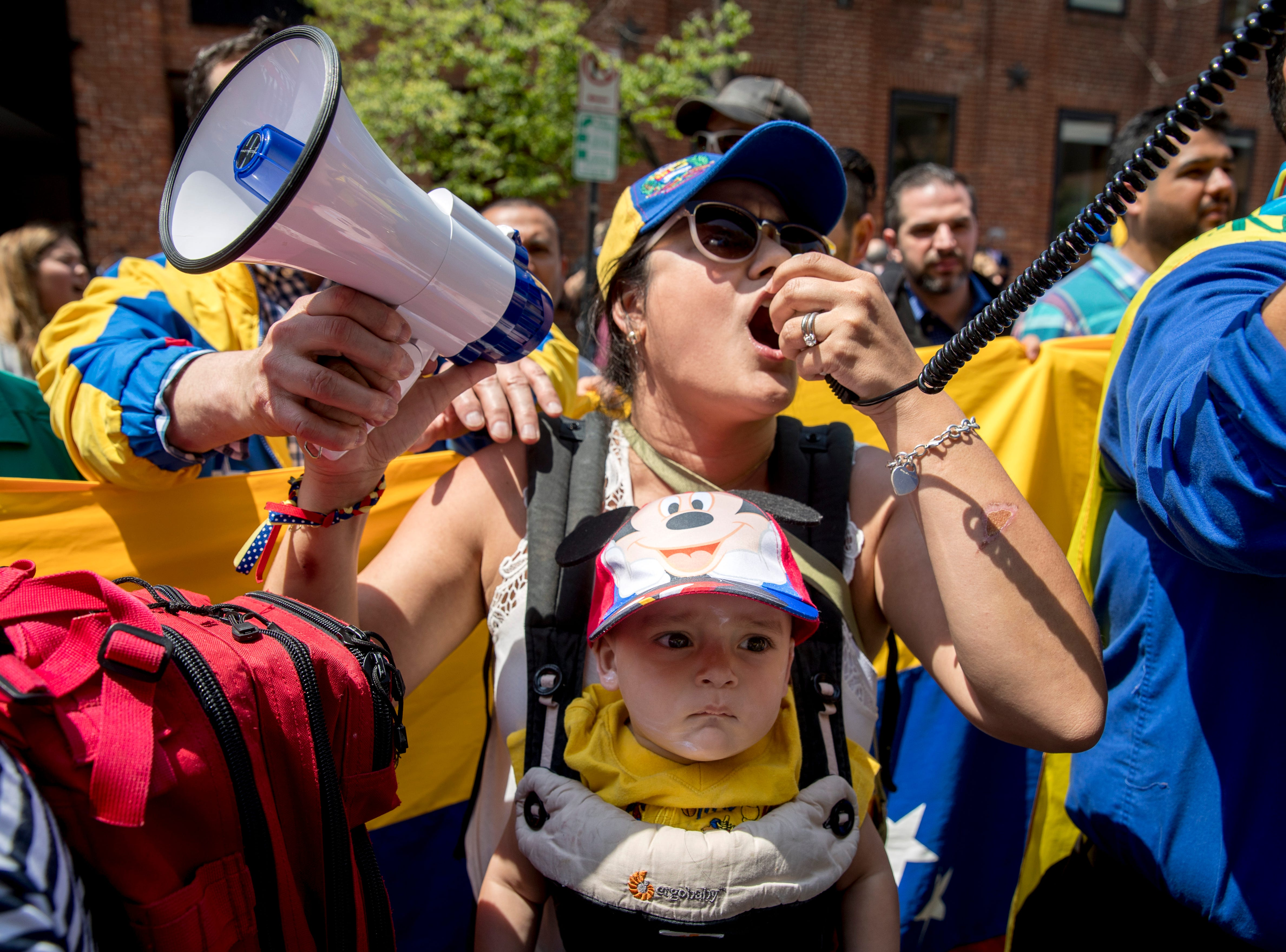 Carla Bustillos of Alexandria, Va., carries her son Carlos as she speaks on bullhorns with other supporters of pro interim government opposition leader Juan Guaido during a rally outside of the Venezuelan Embassy in Washington, Tuesday, April 30, 2019, on the current situation in Venezuela.