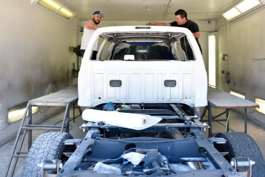 Ulises Rivera, left, and Edwin Ramirez prepare a custom built Ford Excursion for paint at Custom Autos By Tim in Guthrie, Oklahoma on April 26, 2019.