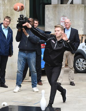IndyCar driver Josef Newgarden shows good form as he makes the winning throw during a game of fowling with former Red Wing defensemen Larry Murphy after a news conference for the upcoming Detroit Grand Prix on Tuesday at Lear Corporation in Detroit.