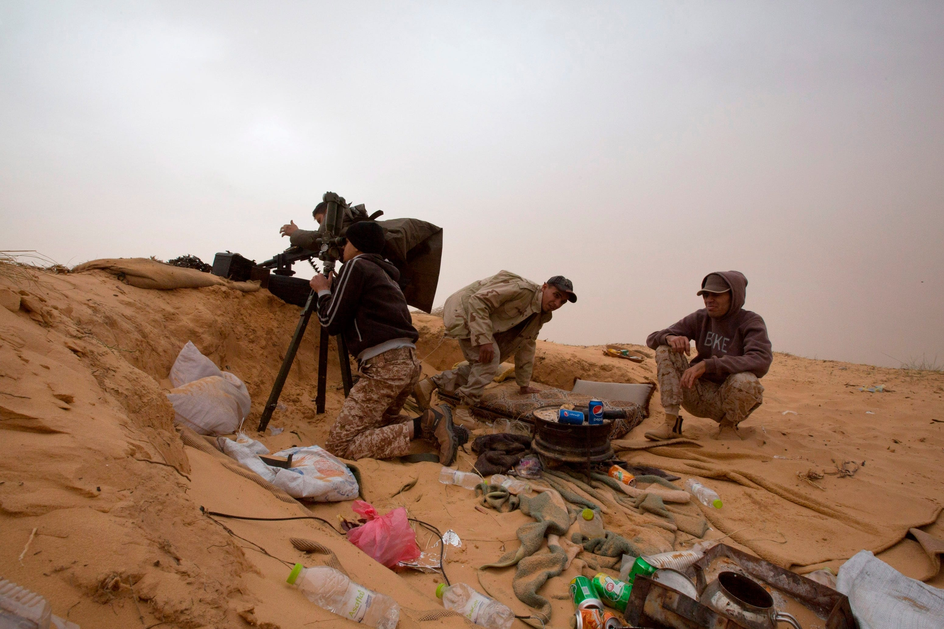 FILE - In this Saturday, Feb. 21, 2015 file photo, Libyan soldiers aim their weapons during clashes with militants on the frontline in Al Ajaylat, 120 kilometers (75 miles) west of Tripoli, Libya. The work of photographer and video journalist Mohamed Ben Khalifa, who was killed in Libya on Saturday, Jan. 19, 2019, reflected Libya's post-2011 chaos of rival militias fighting for control as well as the humanitarian tragedy of waves of people fleeing North Africa, the Middle East and sub-Saharan Africa.