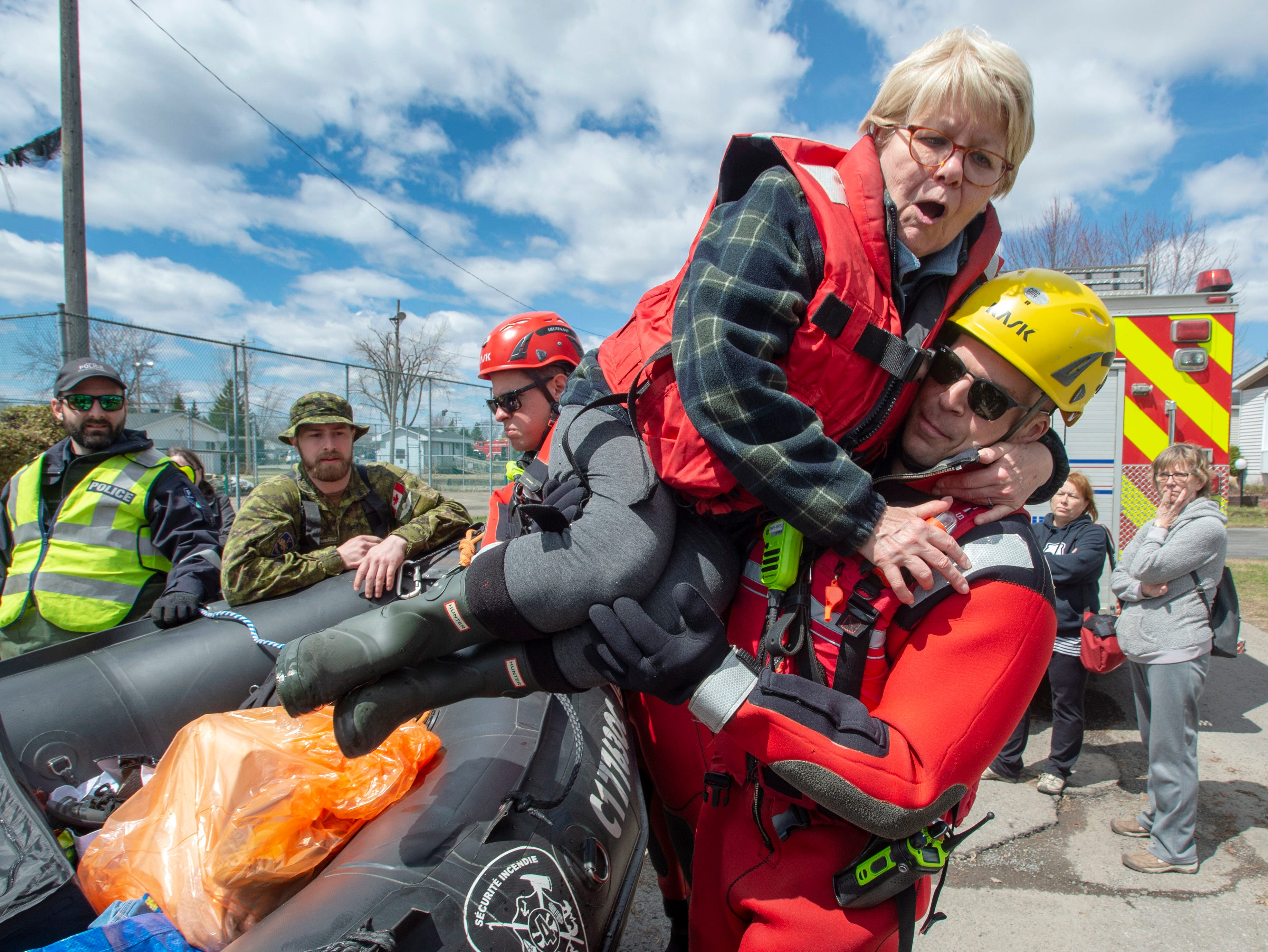 Boisbriand firefighter Alex Turgeon helps Jocelyne Martin out of a Zodiac after retrieving some belongings from her flooded home in St-.Marthe-sur-la-Lac, Quebec on Tuesday, April 30, 2019.