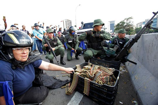 An anti-government protester sits by ammunition being used by rebel troops rising up against the government of Venezuela's President Nicolas Maduro as they all take cover on an overpass outside La Carlota military airbase, Tuesday, April 30, 2019.